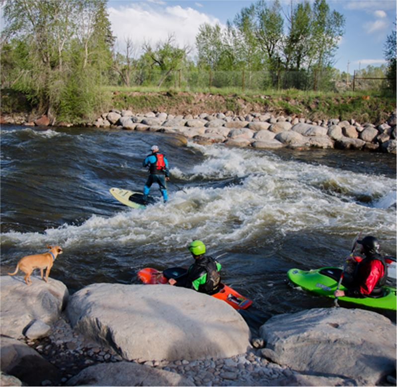 Four kayakers fighting rapids